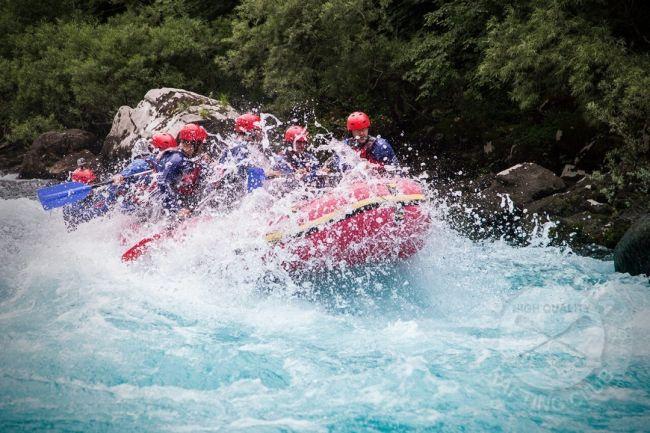 crveni rafting camac se probija kroz svijetlo plavu rijeku Taru i nie lako vidljiv od pjenusave vode, naziru se ljudi u čamcu, svi su zapljusnuti vodom iz brzaka