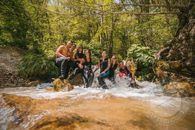 vesela ekipa mladih ljudi stoji na vrhu vodopada čija je voda kristalno čista i sa osmehjehom poziraju za fotografisanje u vodi do koljena
