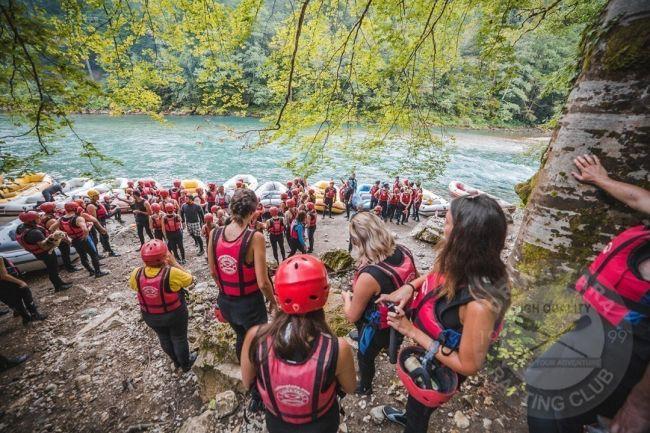 prilazak tirkizno plavoj rijeci koji je pun mladih ljudi u opremi za rafting u manjim grupama