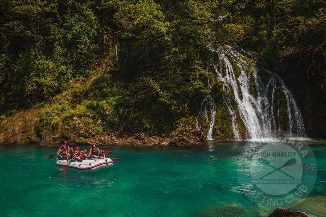 u lijevom uglu je bijeli gumeni rafting čamac na kojem su mladi ljudi, rieka Tara je mirna i jarko zelene boje, na desnoj strani je vodopad koji visok 3-4 metra i razliva se na nekoliko zasebnih mlazova prirodno