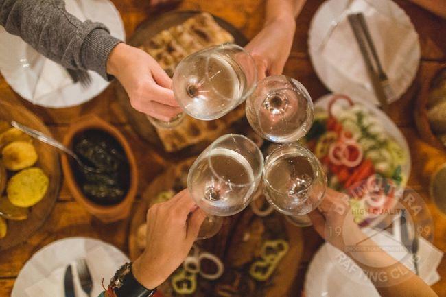 pogled odozgo na četiri čaše bijelog vina koje nazdravljaju iznad prepunog stola hrane servirane za večeru