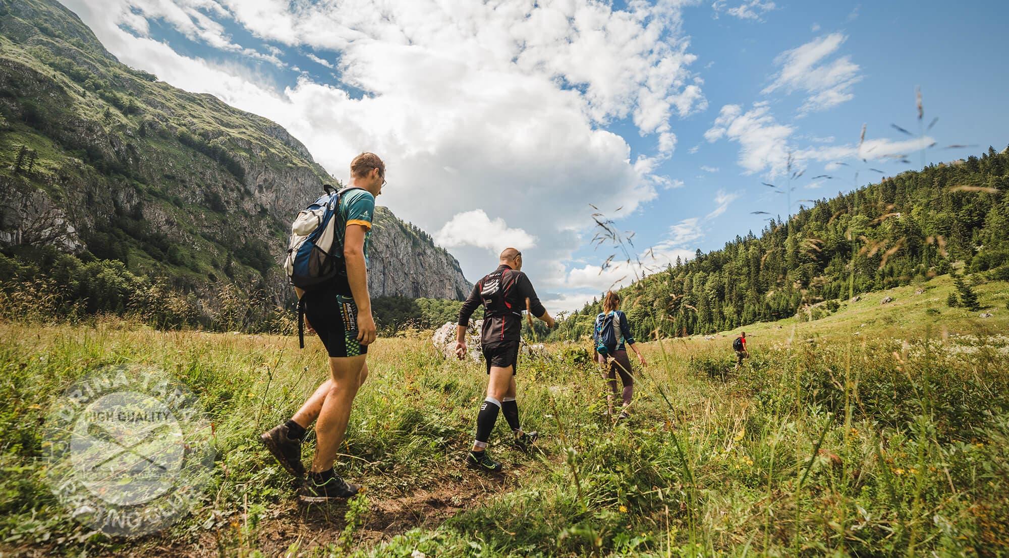 Nekoliko mladih ljudi pjesace planinskim puteljkom u prekraznom pejzazu Nacionalnog parka Sutjeka