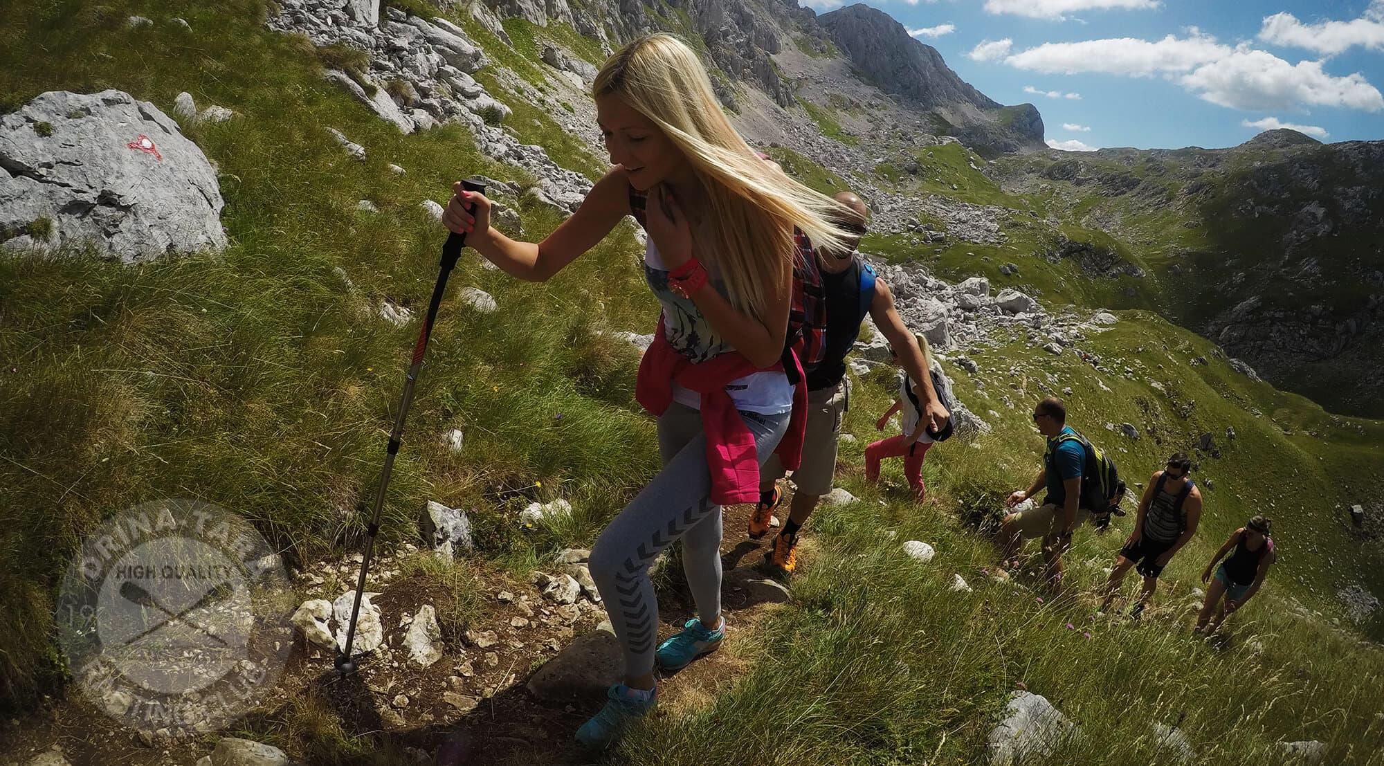 Mladi ljudi se penju uz zelenu planinu jedno iza drugog i svi imaju osmeh