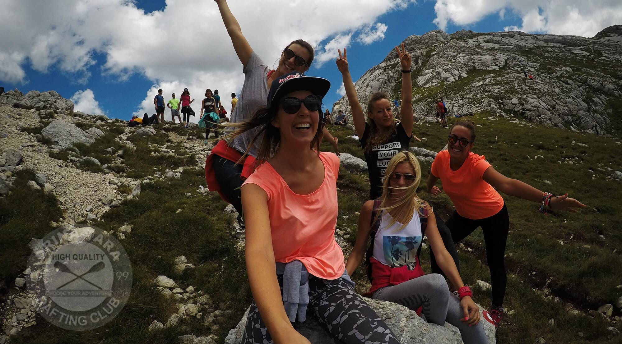 Zeseli mladi ljudi silaze niz planinu i slikaju selfi