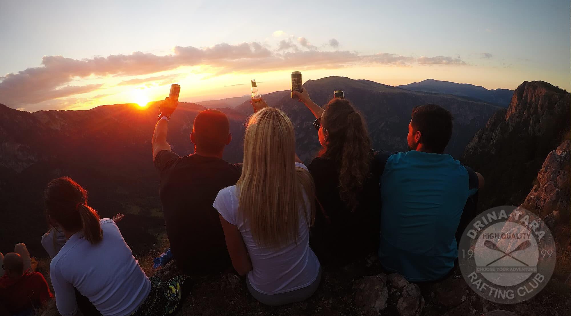 Mladi ljudi na vrhu planine uzivaju u pogledu na zajazak sunca i nazdravljaju