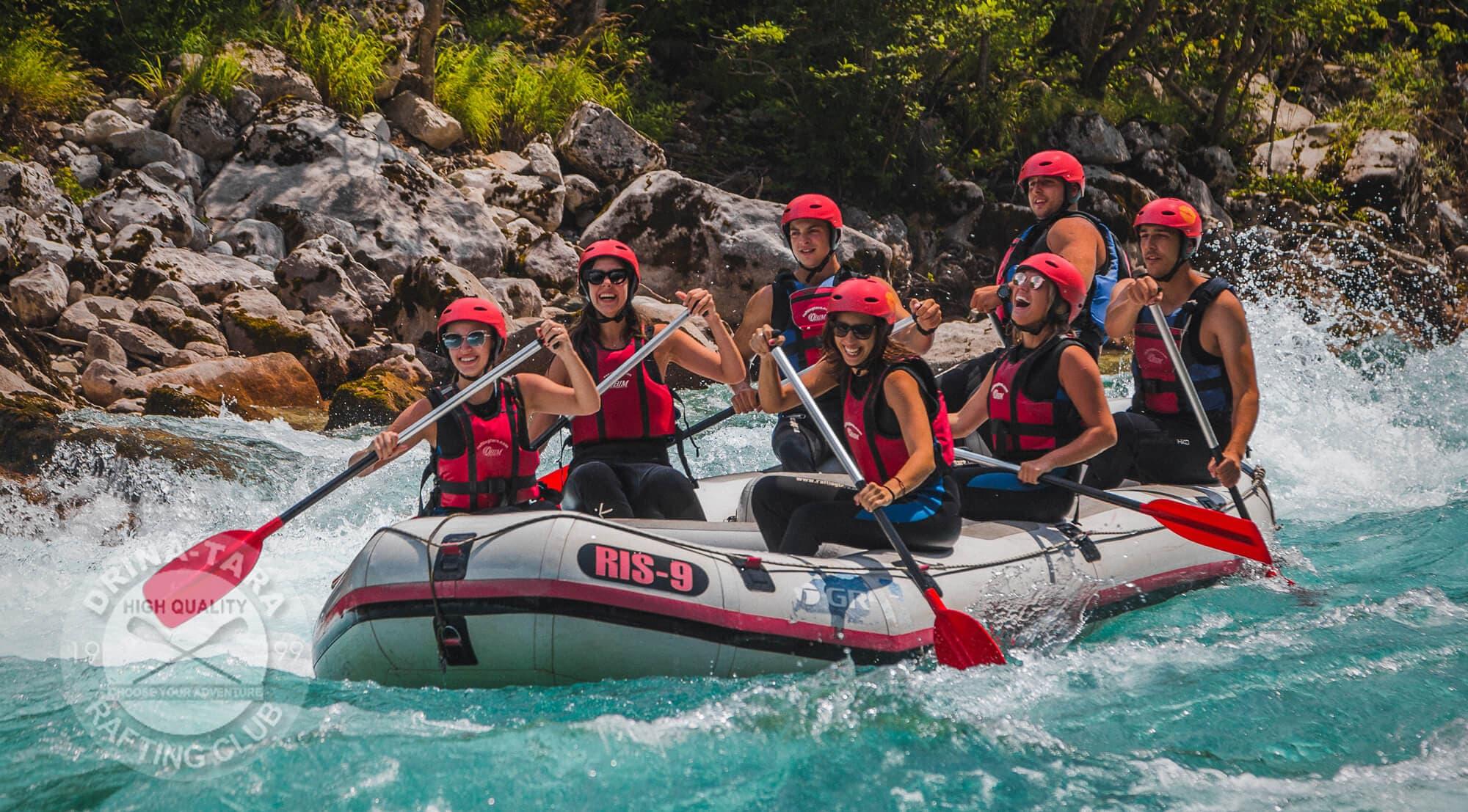 Rafting Tarom na tirkizno zelenoj rijeci Tari mladi ljudi veselo veslaju sa osmjehom na licima